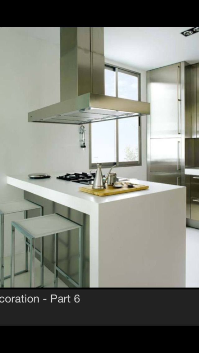 Modern, industrial open layout galley kitchen includes prep counter with gas range, stainless range hood and talk, thin stainless fridge