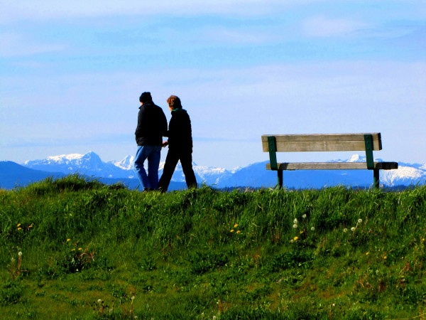 A couple walks along the dyke trail on the Middle Arm Greenway with the snow-capped northshore mountains in the back by RayVanEng, via Flickr