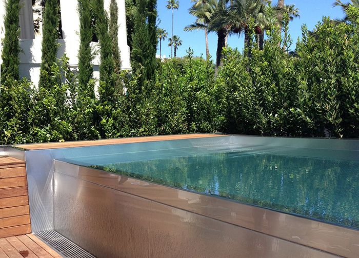 La piscine est bordée sur deux côtés par une végétation dense, qui crée une atmosphère plus intime.