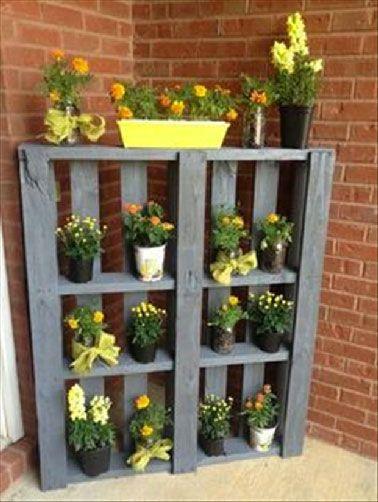 Une palette bois transformée en étagère pots de fleurs dans le jardin