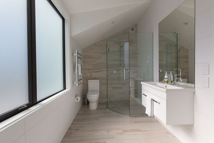 "Stylish bathrooms, interest created by the angular roofing pitch accentuated by the contemporary Colli ""Summer"" tile."