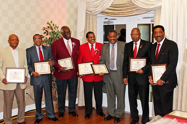 50 YEAR KAPPA ALPHA PSI LINE BROTHERS (Alpha Phi Chapter, Virginia State University) celebrate their anniversary in Reginald F. Lewis's absence. Lewis, a member of this pledge line, passed away in 1993. His younger brother, Tony Fugett, holds Lewis's certificate and stands in for him in this photo. Left to right: Donald Muse, Johnny Davis, Herman Bell, Frankie Boyd, Tony Fugett, Sam Banks and Lin Hart.