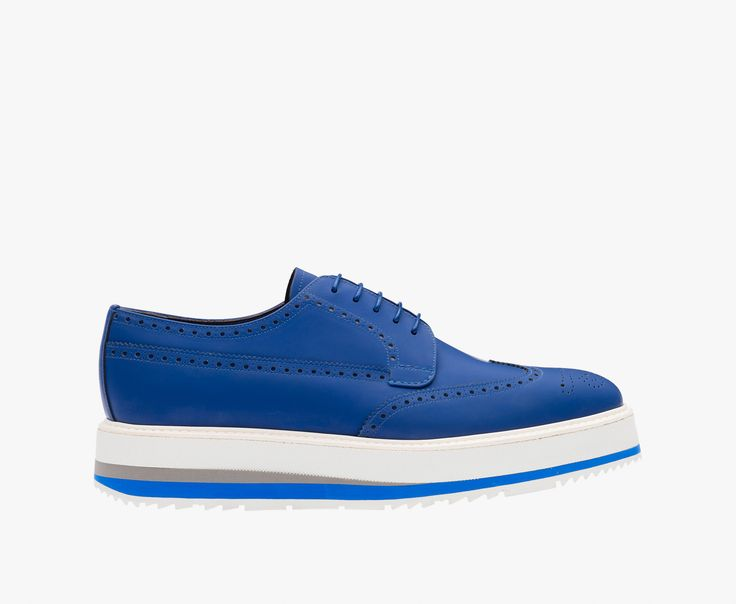 Opaque rubber leather laced derby shoe Perforated wingtip motif on the toe  Covered wedge heel with