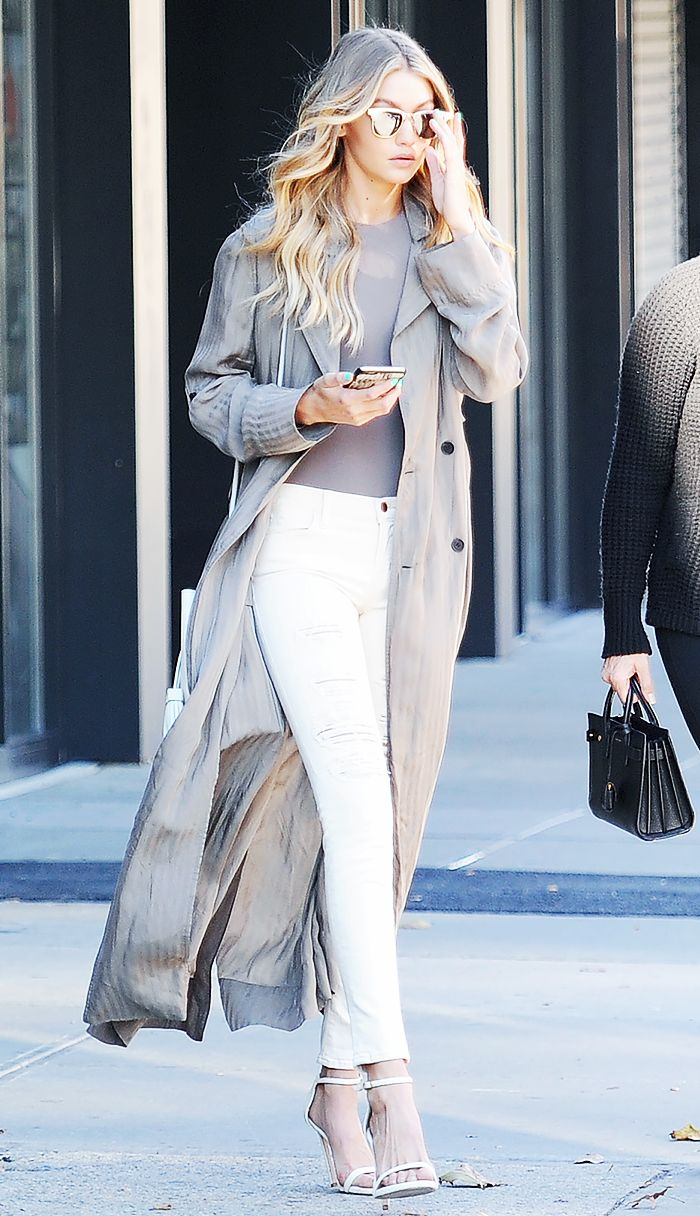 Gigi Hadid wears a t-shirt, long duster coat, white pants, ankle-strap heels, and mirrored sunglasses