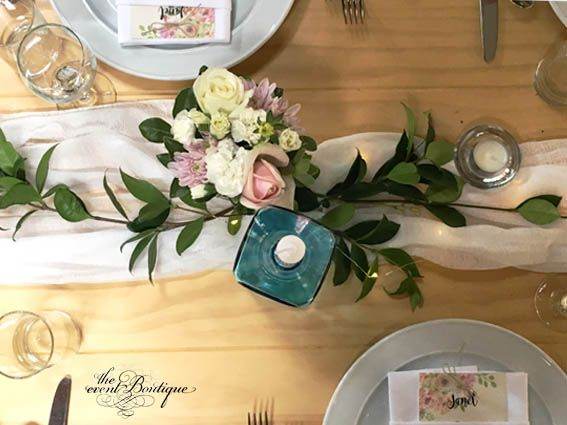 Birdseye view of one area of the table styling. Seed lights were woven under the muslin for a soft romantic look with clustered groups of florals and candles.
