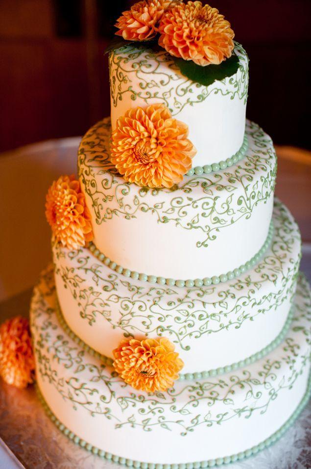Moderne bruidstaart met groene details en oranje/gele bloemen