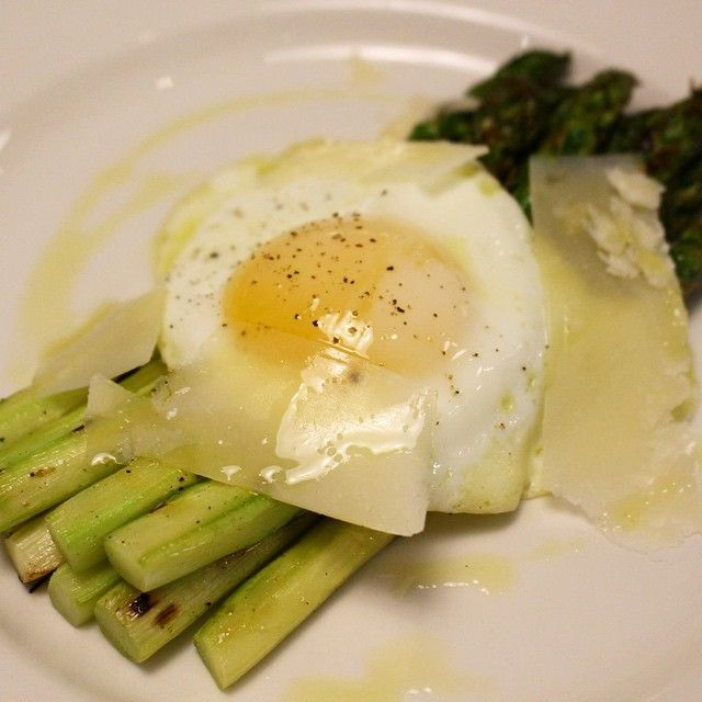 Asparagi alla Milanese: grilled asparagus topped with an oven-roasted egg and shaved Parmigiano Reggiano