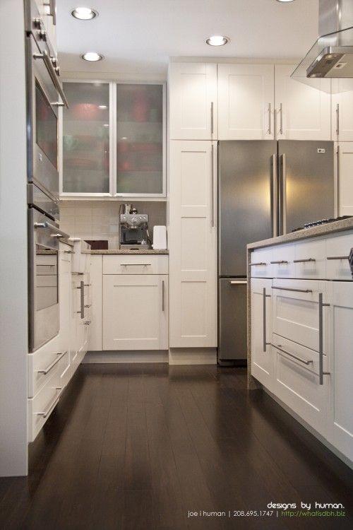 Love the cabinets around the fridge on this! White Cabinets + Dark Wood Floors + Waterfall Countertop