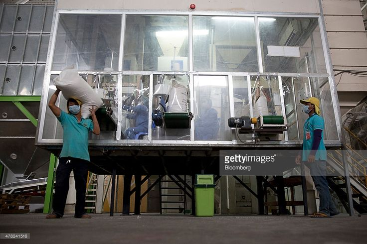 A worker picks up a sack of rice as others sit on conveyors at the Amru Rice Co. processing factory in Phnom Penh, Cambodia, on Monday, June 22, 2015. The 10 members of the Association of Southeast Asian Nations (ASEAN) are seeking to implement the Asean Economic Community by the end of the year. Officials are working to allow free movement of goods, services, investment, capital and skilled labor as part of a European Union-style integration plan, without a common currency. Photographer…