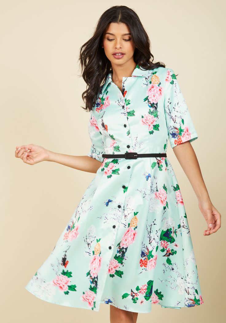 Boldly showcase your appreciation for past fashion with every wear of this mint shirt dress. A vintage-inspired look to captivate even the most modern-minded gal with its half sleeves, matte black buttons, and gorgeous floral print, this satin midi is a testament to nostalgic sophistication!