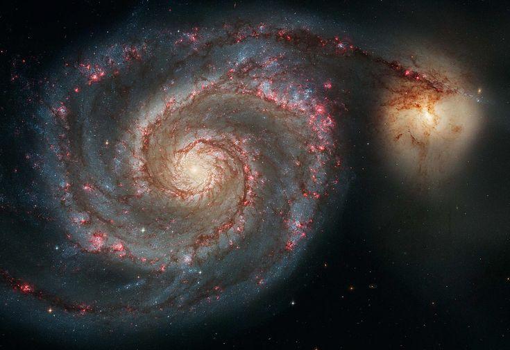 Galáxia do Rodamoinho e sua companheira  Astrônomos acreditam que os braços da Galáxia do Rodamoinho são tão proeminentes que praticamente alcançam a pequena M51, amarela, à direita.