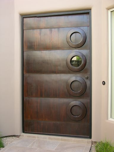 """Sculptor Kevin Caron created this steel door with a natural rust finish for an architect who was remodeling a Scottsdale, Arizona, home. One of the """"donuts"""" is the handle, another a window."""