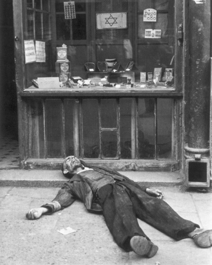 Dead man lies in front of a shop in the Warsaw ghetto. The photo belongs to a collection of images by Heinrich Joest and Willy Georg, two German soldiers who took to the streets of the ghetto with a camera.
