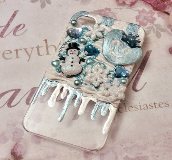 """This winter-inspired design is one of the most popular during the Christmas season. Blue and white paints alternate to mimic an """"icicle-theme"""" drizzle, while a handmade crowned heart, snowman, and snowflakes sit on a field of artificial snow. Tiny pearls or jewels are used as a garnish to complete the design."""