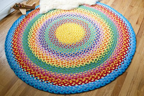 """T-shirt rug, braided from 1.5"""" strips and machine sewn together with zig zag stitch. She said it was time consuming and frustrating, but it is so cheerful! She links to a tutorial."""