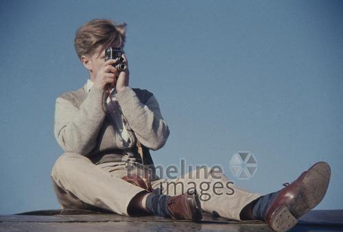 Ein junger, finnischer Mann filmt sitzend mit seiner Filmkamera, 1959,  hgra60/timeline-images #1950er #1950ies #Doppelauge #historisch #historical #Doppelobjektiv #Film #filmen #Filmkamera #Finne #Herrenmode #Mann #Mode #Urlaub #sitzen