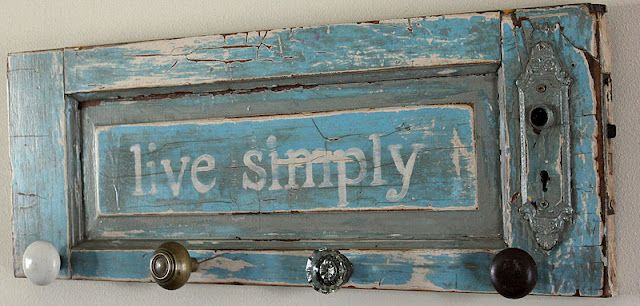 Old cabinet door repurposed to a coat hanger.  Love this color, quote and knobs for hangers