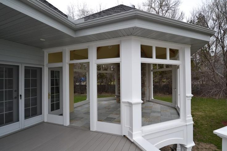 enclosed deck area with stone tile floor (keeps bugs out) and fireplace and big windows