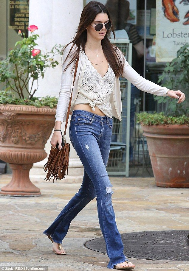 Boho chic: Kendall Jenner channeled the 1970's, wearing flared denim and a fringe leather handbag