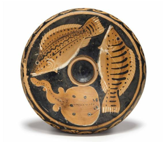 Paestan fish plate, red-figured, workshop of Asteas and Python, 350-330 B.C.  With a striped bream, a coris and a torpedo, a band of wave on the overhanging rim, details in added white, 20.3 cm diameter. Private collection