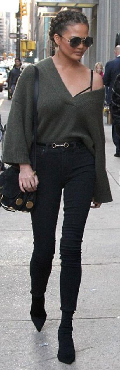 Who made Chrissy Teigen's green v neck sweater, black skinny jeans, ankle boots, belt, and gold handbag?