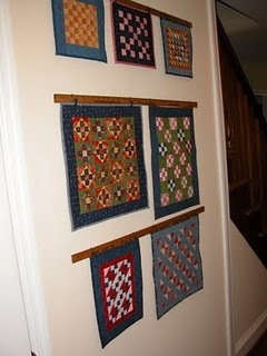 Using vintage yardsticks to hang little quilts on the wall. Great idea!