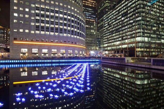 London Paper Boats 3  Aether & Hemera   Installation at London's Canary Wharf, presented until 15 February 2013. Called Voyage, this beautiful creation offers a fleet of 300 boats illuminated recalling the form of paper boats that can change colors.