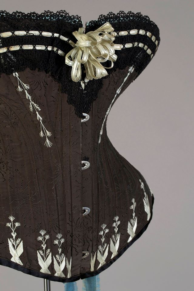 1880s, Poland  Corset by Marie Grochovska  Black silk brocade with blue embroidery, black lace trim and blue elastic self suspenders  Kent State University Museum