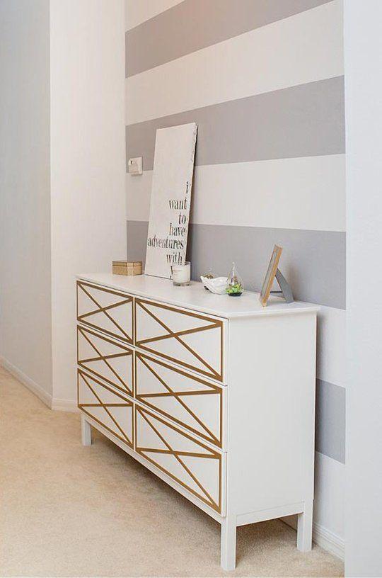 Mur rayé et meuble blanc et or