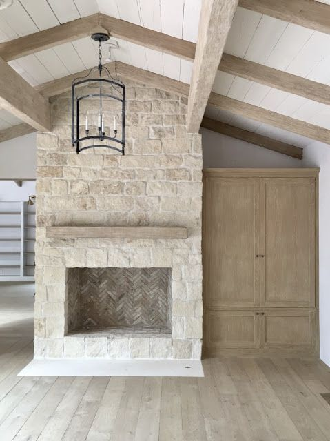 stone fireplace beams chandelier bleached oak floors built-ins