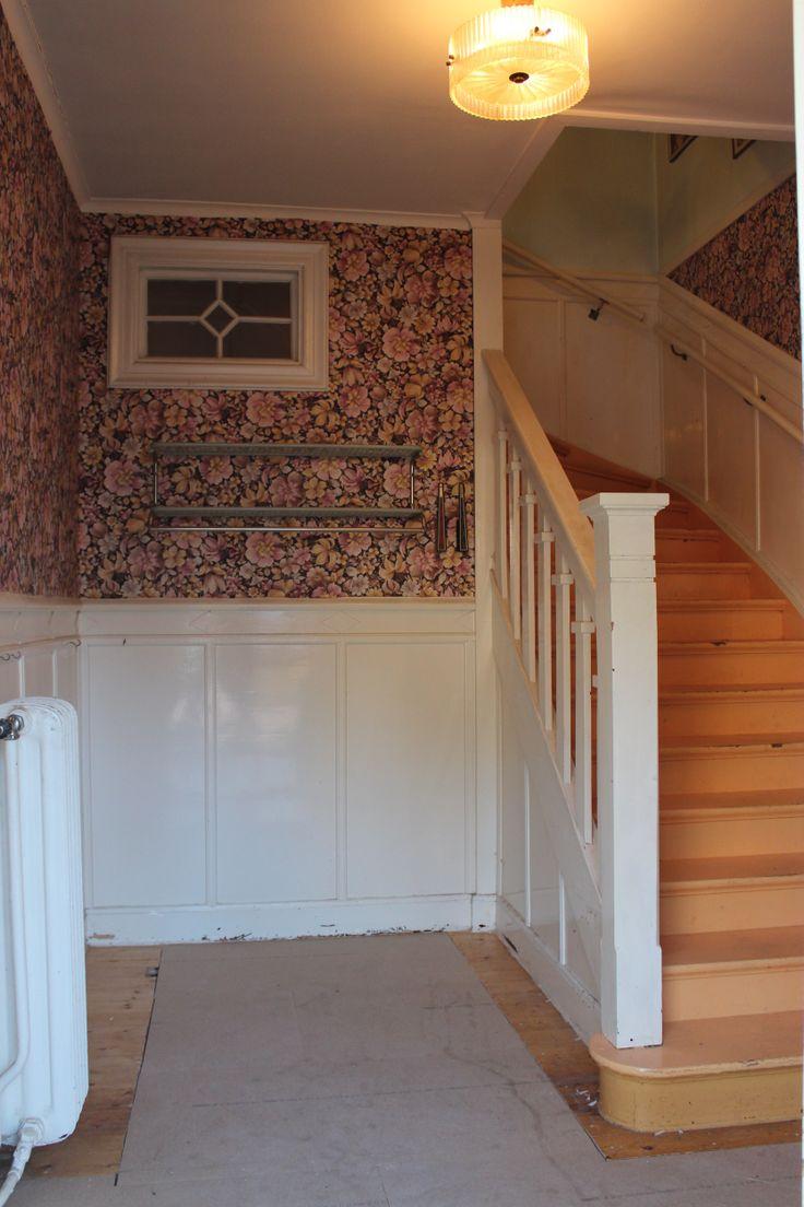 Förvaringsdel i hall vid vacker trä-trappa och bröstpanel. Litet fönster mot källartrapp. Blommig söt 70-tals tapet. Tjusig äldre takplafond.