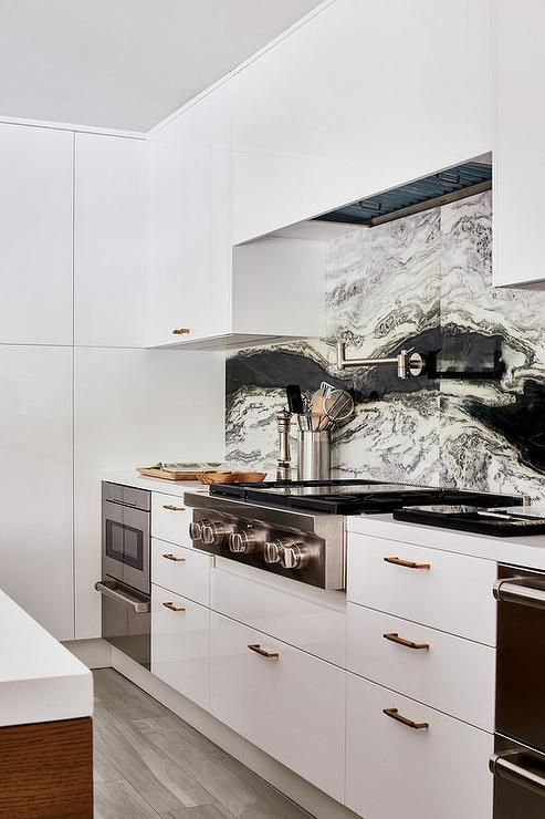 Beautiful contemporary kitchen features white flat front cabinets accented with brass hardware and fitted with a stainless steel cooktop positioned against a white and black marble sliding backsplash beneath a satin nickel pot filler and a white concealed hood flanked by white flat front upper cabinets.
