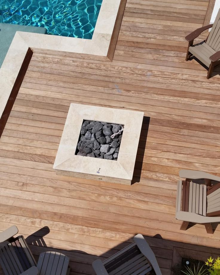 Travertine creates clean lines and a high-end look for this square fire pit on a pool deck made of ipe wood. Volcanic rock fills the natural gas fire pit, which has a stainless steel burner. The modern fire pit and pool area is designed by Atlanta-based Hearthstone Environments.