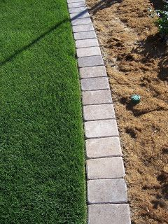 Mow strips can be made from any solid material used to separate the lawn from a planting bed. They allow a law mower to trim the grass all the way to edge of the lawn without having to use a string trimmer. Mow strips are usually made from concrete but can also be made from pavers