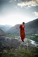 Woman wearing a local red dress. In Khorog town, capital of the Pamir and home of the Ismaili community...Tajikistan and the Tajik Pamir mountains (province of Gorno Badakhshan), summer 2009.