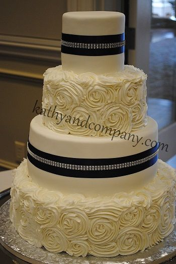 Fondant and rosette wedding cake with navy ribbon and bling.