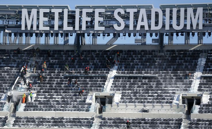 Description of . Workers shovel snow off the seats at MetLife Stadium as crews removed snow ahead of Super Bowl XLVIII following a snow stor...