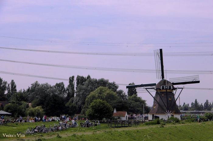 Everywhere I look bikes are parked against trees or dropped on the grass. As the anticipation grows, more people gather near and around the area of the windmill. What are they waiting for? #typical #Dutch #landscape #event #favouritespot