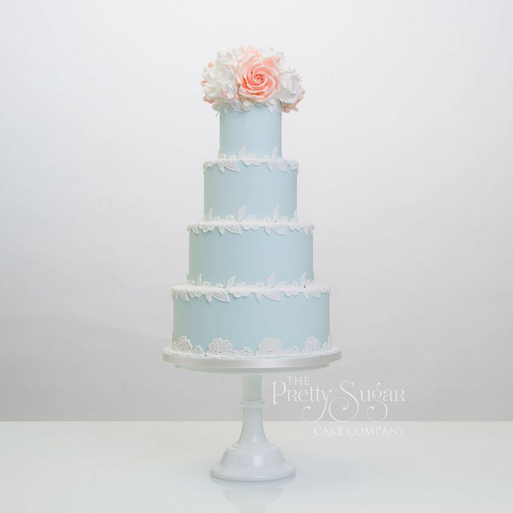 Pale aqua wedding cake with white lace and peach and white sugar rose bouquet