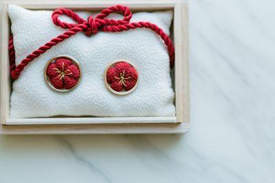 指輪 : makky☆のはっぴーらいふ♪ ①箱のサイズにあわせて切った白いちりめん布を2枚を用意し、  表合わせに重ね、裏側の四隅を縫います。  1センチ程空けておいて裏返し、バランスを見ながら綿を入れてまつり縫い。  箱にぴったりおさまるちっちゃい枕の様なものをつくります。  ②赤いちりめん布を丸く切った赤い布の橋をざくざくと縫って綿を詰めながら絞り、  梅を作ります。  梅の作り方はここのを参考にさせてもらいました→ファミリアミアさん(*´艸`*)    ③桐箱の蓋の部分に合わせた厚紙を切り、  あらかじめちりめん布に梅の刺繍とミニ寿ハンコを押してあった布を  厚紙にボンドで貼り付け、蓋に両面テープではりつける。  ④紐をあえて、リボンにし・・・(*´艸`*)かわゆす♪ ⑤最後に桐箱に寿ハンコをポンっ!