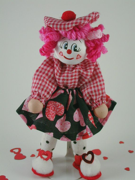 Valentine Girl Clown is dressed in very cute Valentine fabric. I love the poka dot socks. Cheeky is what I would call her with tiny hearts.... She is 5 1/2 inches tall with movable arms and legs. Comes with a metal stand and some heart confetti for display.
