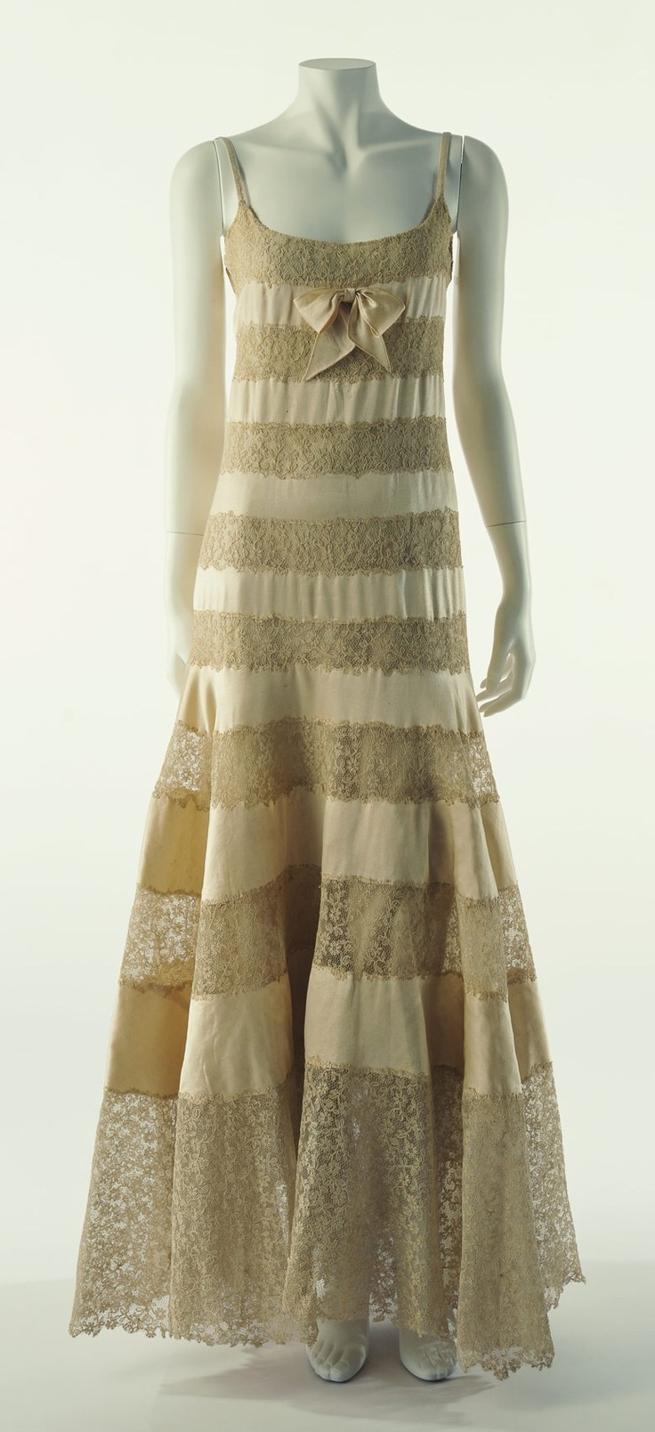 """Evening Dress, Gabrielle Chanel, Paris, France: ca. 1930, alternately-pieced silk satin and lace. """"This elegant evening dress from the 1930s has insertions of lace, the technique which was frequently used for lingerie during the Belle Époque period. Of the camisoles, slip dresses, and other similar styles that have transformed to become modern day outerwear, this work was the first such underwear fashion piece of the modern era..."""""""