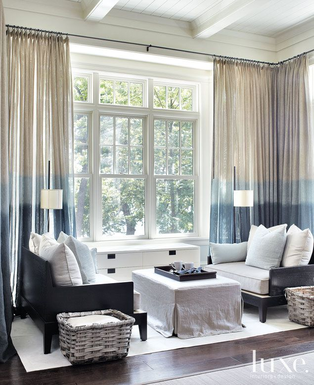 This small seating nook on the outskirts of the great room has spectacular lake views. The extra-roomy daybeds swathed and driftwood finished baskets further accentuate the nautical tone. A carpet in a neutral hue grounds the vignette.