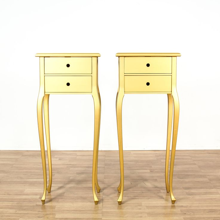 This pair of nightstands is featured in a solid wood with a shiny gilt finish. Each contemporary style bedside table has 2 spacious drawers, extra long sabre legs, and carved out knobs. Unique pieces that are perfect with a super tall bed! #contemporary #dressers #nightstand #sandiegovintage #vintagefurniture