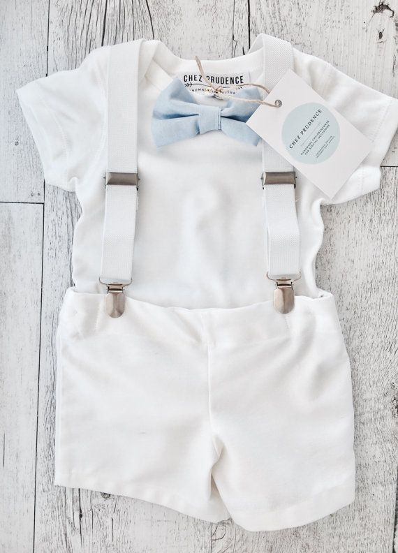 Traditional white with a vintage cool vibe this baby boys suspenders, onesie, bow tie and pants outfit will stand out at any christening! Super comfortable means your baby will enjoy the special occasion even more. This set includes the short sleeve onesie, shorts, suspenders and bow tie. Matching shoes and paper boy cap available also. Set will include the pale blue bow tie unless other colour requested. Bow tie options are (shown in the photo) Light grey, light blue, white or blue pin...