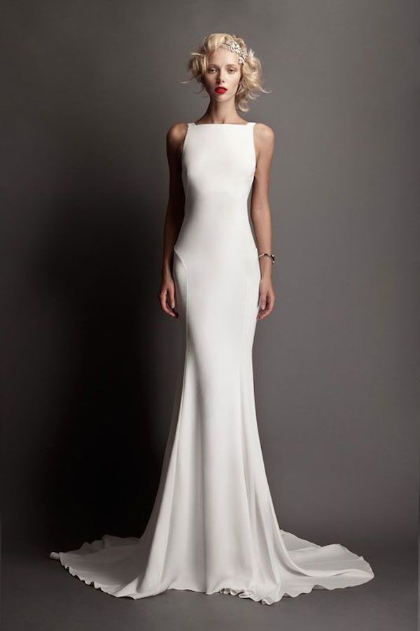 This body skimming sheath is so simple yet there's something that keeps our eyes drawn to it like a magnet. The height of the bateau neckline of this wedding dress lends an air of understated elegance that few dresses can compete with.