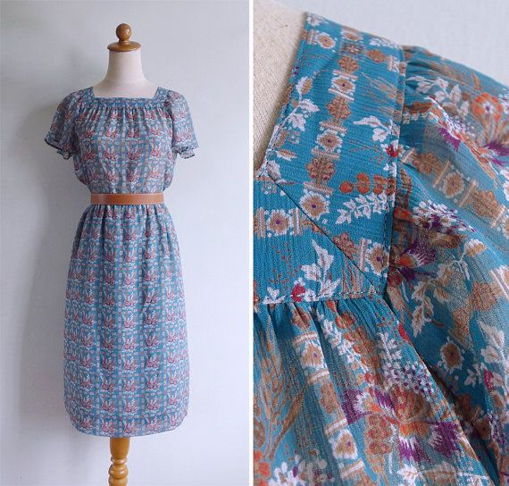 Lots of great details on this 1980s day dress!  Teal green polyester chiffon with a pretty floral print. Features striped patterns of ornate