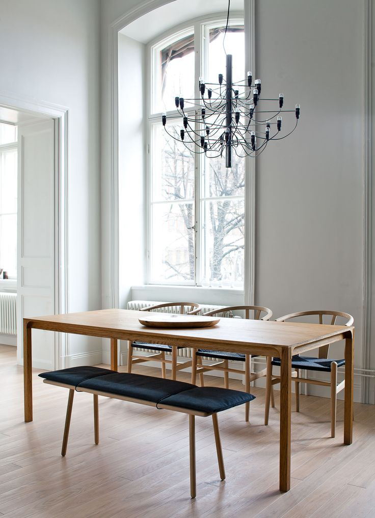 This sunlit interior features the FLOS 2097 pendant light, a wood table, light wood floors and bench seating.