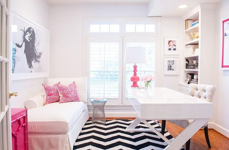 White and pink office features a white lacquered desk, Z Gallerie Jett Desk, topped with a hot pink lamp and a tufted desk chair atop a black and white chevron rug.