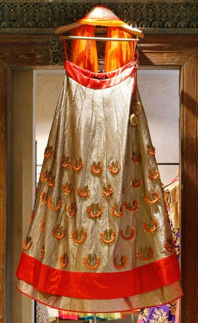 Light Lehengas - Gold Foil Lehenga | WedMeGood | 3-D Lotus Motifs on a Gold Foil Lehenga wit Orange Border and Orange Dupatta #wedmegood #indianbride #indianwedding #lehenga #gold #orange #lotus